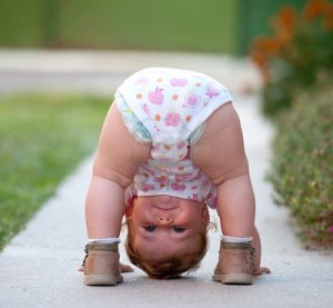 16764235-one-year-baby-girl-playing-upside-down-on-the-street